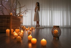 Young woman standing in room with burning candles on floor