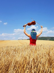 young woman standing in rye field and holding violin above head