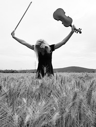 young woman standing in rye field and taking a bow with violin in hand