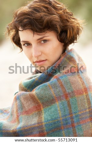 Young Woman Standing In Sand Dunes Wrapped In Blanket