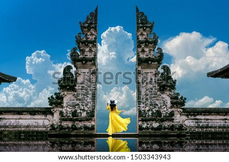 Young woman standing in temple gates at Lempuyang Luhur temple in Bali, Indonesia. Vintage tone.
