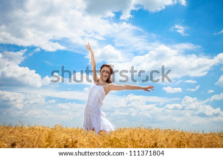 Young woman standing in wheat field with arms outstretched