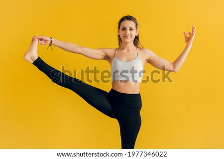 Young woman standing in yoga asana utthita hasta Padangusthasana, extended hand to big toe yoga pose , studio shot, yellow background Foto stock ©