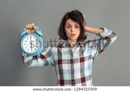 Young woman standing isolated on grey wall showing time on alarm clock touching head looking camera mouth opened concerned