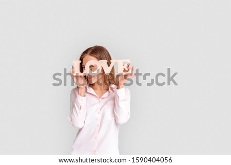 Young woman standing isolated on white background holding love sign looking through the hole to camera smiling playful