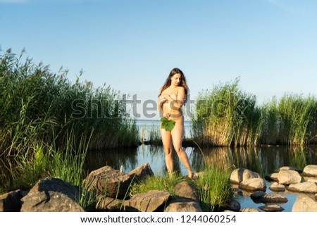 Young woman standing naked at stones with green grass and blue sea as backgroung with her hand and leaf covering as the famous Venus paintings