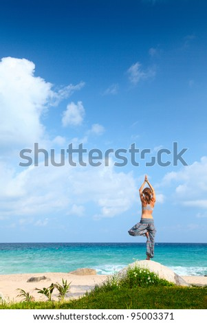 Young woman standing near a beach and stretching