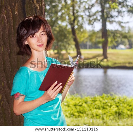 Young woman standing near a tree with a book in a summer park