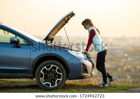 Young woman standing near broken down car with popped up hood having trouble with her vehicle. Female driver waiting for help beside malfunction auto.