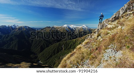 Young woman standing near mountain top overlooking peaks beyond