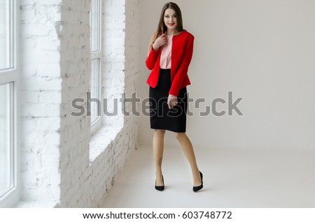 Young woman standing near the window, wearing shirt, jacket and skirt, have a long hair #603748772