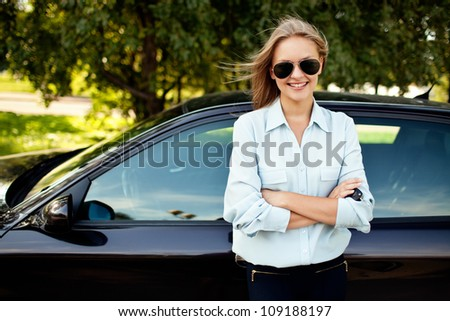 Young woman standing next to her new car