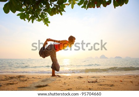 Young woman standing on a beach and doing yoga exercices