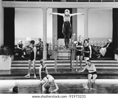 Young woman standing on a diving board surrounded by a group of people playing