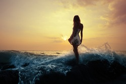 Young woman standing on a rock in sea and holding her dress. Toned