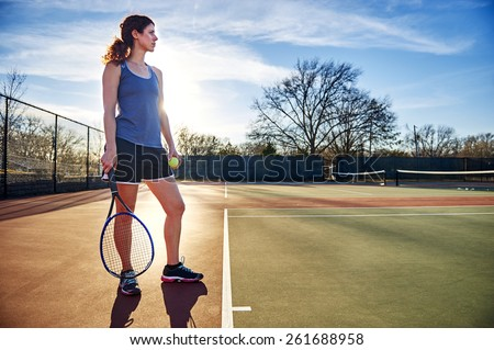 young woman standing on a tennis court