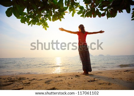 Young woman standing on a tropical beach with rised hands and looking to a sun