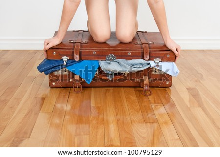 Young woman standing on her knees on overfilled suitcase, trying to close it.