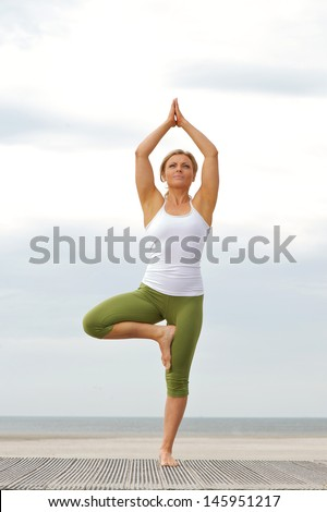 young woman standing on one leg in balance yoga pose