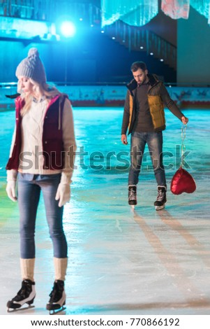 young woman standing on rink while boyfriend with heart shaped balloon standing behind #770866192