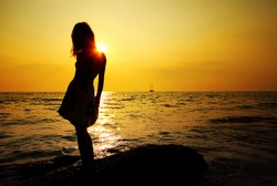 Young woman standing on rock in sea and looking to a sun