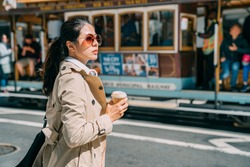 Young woman standing on street drinking coffee to go while putting headphones on neck. beautiful elegant female commuter waiting for taxi on road. blurred view driving cable car in san francisco back