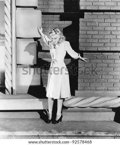 Young woman standing on the ledge of a building and looking feared