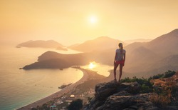 Young woman standing on the top of rock and looking at the seashore and mountains at colorful sunset in summer. Landscape with girl, sea, mountain ridges and orange sky with sun. Oludeniz, Turkey