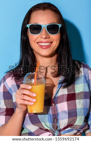 Young woman standing wearing sunglasses having bare belly isolated on blue wall holding glass drinking smoothie looking camera smiling cheerful close-up
