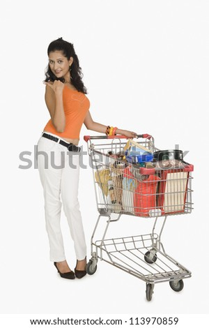 Young woman standing with a shopping cart and pointing