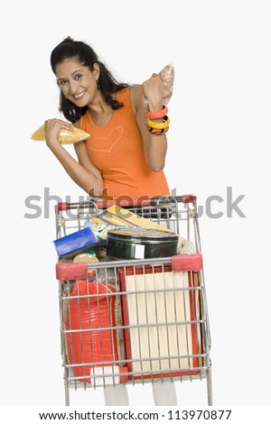 Young woman standing with a shopping cart and smiling