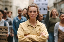 Young woman standing with arms crossed standing in a rally. Woman protesting with group of activists outdoors on road.