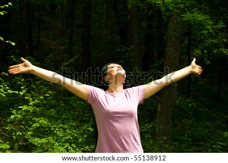 Young woman standing with arms open  and eyes closed to breath the clean air  from a spring forest