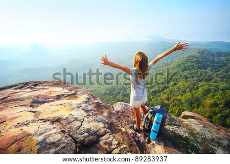 Young woman standing with backpack on cliff's edge and looking to a sky