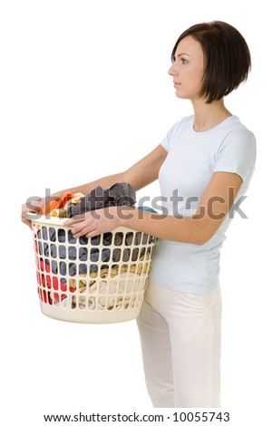 Young woman standing with full laundry basket. She looking ahead. Side view, white backgroun.