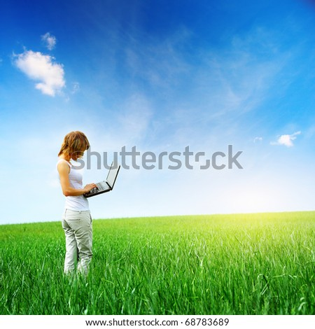 Young woman standing with laptop on a green meadow