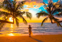 young woman standing with palm tree in the beach during sunset of beautiful a tropical beach