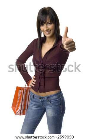 Young woman standing with shopping paper bags and showing OK by hand. Isolated on white in studio.