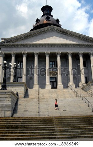 Young woman stands on the steps of the capital of South Carolina in Columbia.  She is looking back at the building.