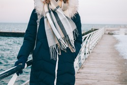 Young woman stands on the winter promenade against the sea, dressed in a down jacket, hood, gloves and warm scarf. Walk in cold season in warm clothes. Pier and seafront with snow on the background.