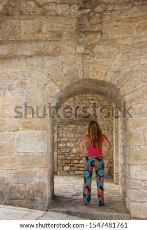 Young woman stands under one of the arches of Porta San Giacomo, Bergamo old town, Lombardy, Italy