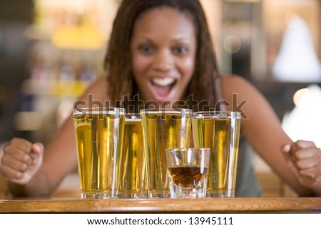 Young woman staring excitedly at a round of beers