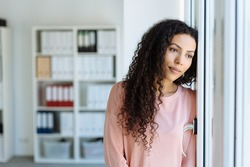 Young woman staring longingly through a window with a sad faraway expression as she leans against a wall in an office