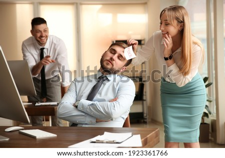Young woman sticking note with word Fool to colleague's face in office. Funny joke