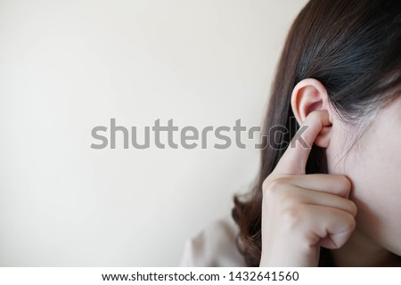 Young woman sticking plug fingers in ears and not listening to loud sound over white background w/ copy space. Loud noise can cause hearing loss, tinnitus or ear pain. Health and medical concept.