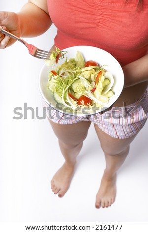 Young woman stood eating a bowl of healthy salad containing lettuce,red peppers,cucumber,tomatoes,and frisee