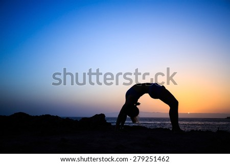 Young woman stretches yoga bridge pose, sunset silhouette in mountains. Motivation inspiration, sport and fitness stretching exercising outdoors in nature.