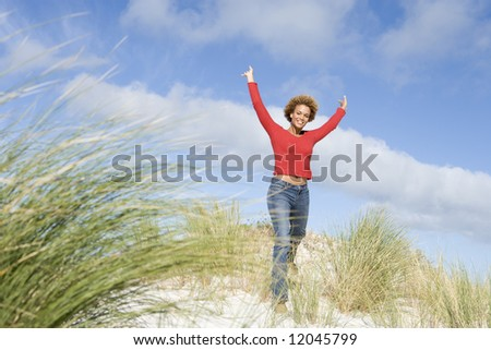 Young woman stretching amongst dunes on beach