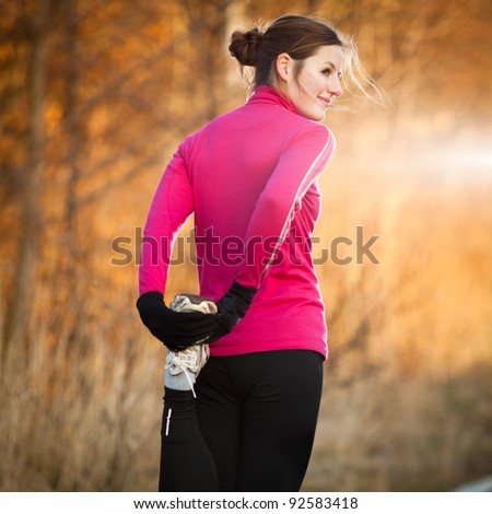 Young woman stretching before her run outdoors on a cold fall/winter day