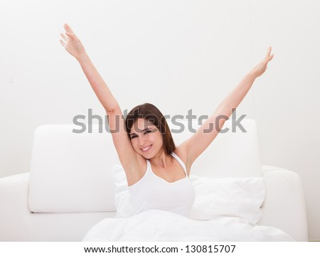 Young Woman Stretching Her Arms In Bed
